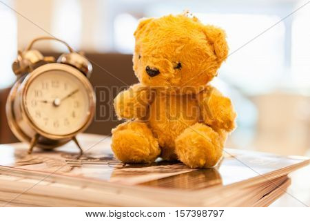 Retro Teddy Bear toy alone with alam clock in lunch time on vintage wall background.