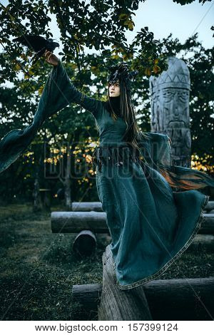 Woman-shaman with horns in green dress walk in forest