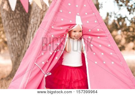 Smiling baby girl 3-4 year old playing outdoors in wigwam