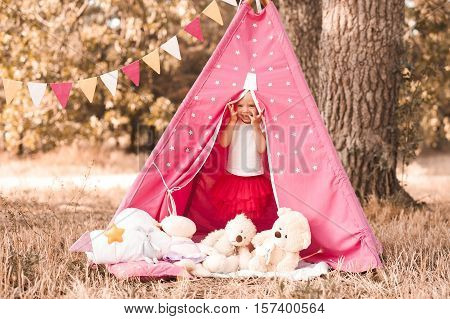 Smiling baby girl 3-4 year old hiding with toys in wigwam outdoors. Playful. Childhood.