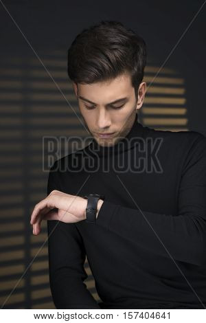 Stylish young man in a black sweater sits near blinds and looks at watch