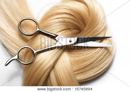 tesouras e close-up de cabelo longo loiro