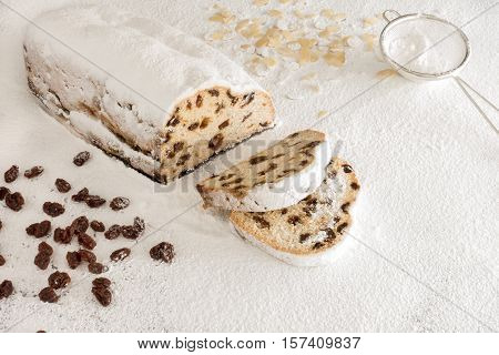 Christstollen with two slices cut off on White Icing Sugar surrounded by almond slivers raisins and a small stainless steel sieve.