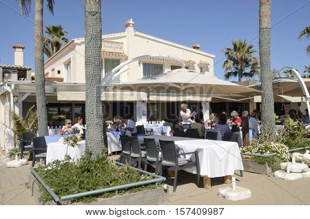 MARBELLA, SPAIN - APRIL 9, 2016: People having lunch at the terrace of a restaurant in the beach of Marbella a city in southern Spain Spain