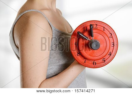 Beginner female athlete holding dumbbell with clock dial. Time for fitness.