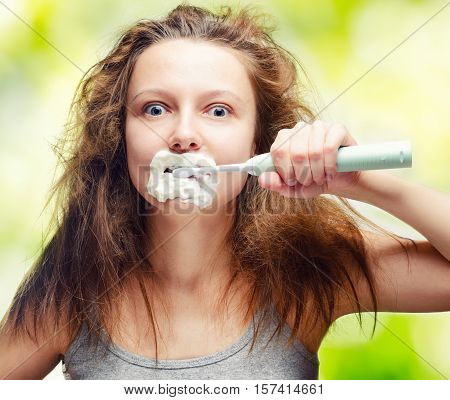 Shaggy pretty young woman using electric toothbrush.