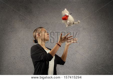 Pretty happy young blond woman in casual cloths catches plush cat toy with heart dreaming looking up against grey texture wall background with copy space horiontal view