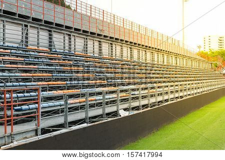 Football stadium with row of seats blue and orange color. This is a public place Does not require a property release. process in soft orange sun light style