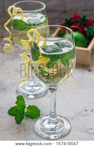 Spritzer cocktail with white wine mint and ice decorated with spiral lemon zest vertical