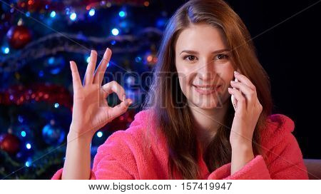 Happy woman talking on cell phone gesturing OK sign, with Christmas tree on background