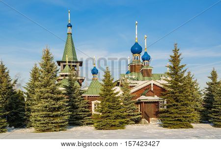 Small log church with blue domes among the fir trees