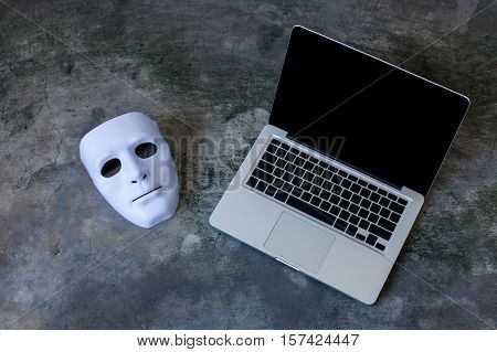 Anonymous mask to hide identity on computer laptop - internet criminal and cyber security threat concept.