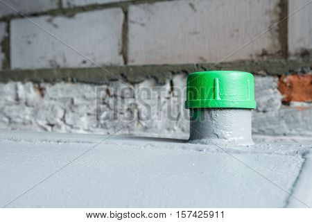 in a separate room in a old building there is a heating oil tank and a filler green cap in closeup