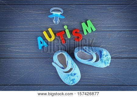 Word AUTISM with pacifier and shoes on wooden background