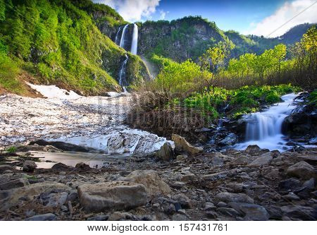 Long Exposure image of a Waterfall at small river near Rosa Khutor resort in Caucasus mountains, Krasnodar krai, Russia - water poetry nature background