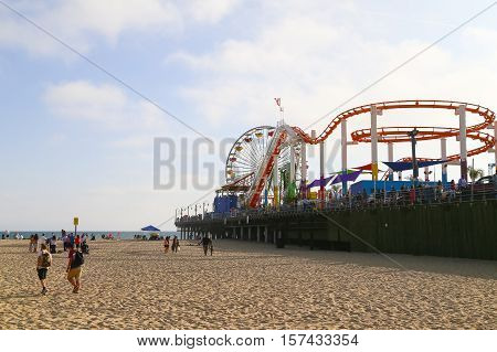 SANTA MONICA, USA - MAY 30, 2015: Santa Monica Pier seen from the beach with people on the beach and on the pier.