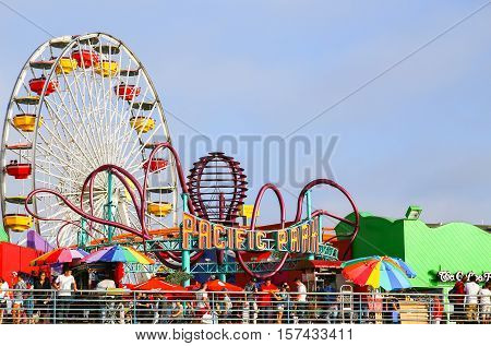 SANTA MONICA, USA - MAY 30, 2015: Entrance of Pacific Park amusement park on the Santa Monica Pier with the Ferris Wheel and the rollercoaster.
