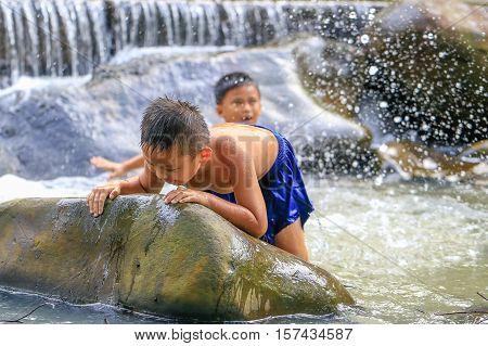 Penampang,Sabah-Oct 29,2016:Kids enjoying and having fun with waterfall in Babagon river,Penampang,Sabah on 29th Oct 2016.