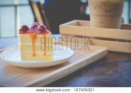 Sponge cake with cherry syrup. Peace of cherry cake served in afternoon time. Cherry cake in cozy outdoor cafe.