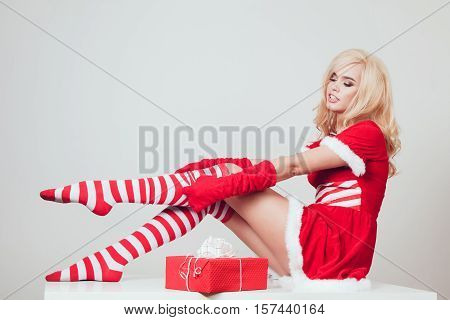 Beautiful blonde snow maiden with gift sits and straightens stockings on a white background
