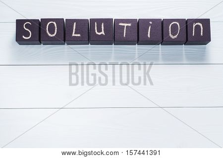 Word Solution from wooden blocks on blue wooden boards with copy space top view. Conceptual of business education and innovation. Word Solution written in chalk on black wooden cubes flat lay.
