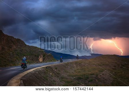 Three travellers on bicycles cycling on a road in asia during stormy weather