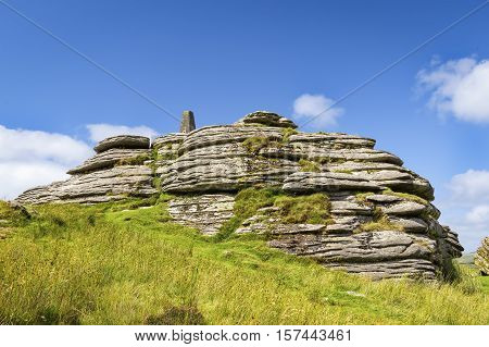 Close-up view of Bellever Tor in Dartmoor national park in southwest England. Copy space in clear sky.