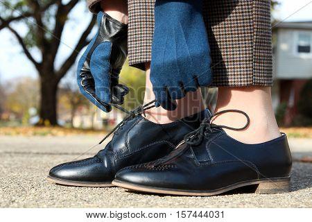 elegant woman in fashion wool gloves tying shoelaces