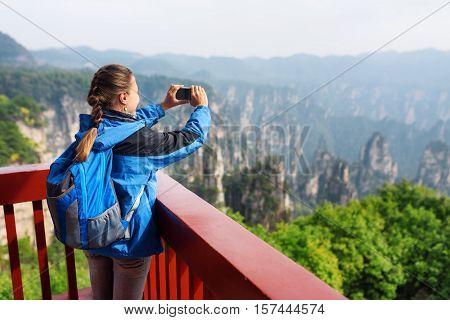 Young Female Tourist Taking Photo Of Zhangjiajie Mountains