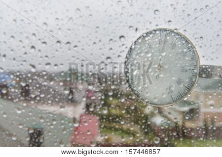 Closeup photo of household alcohol thermometer showing temperature in degrees Celsius with rain drops on glass. Cold weather and forecast concept