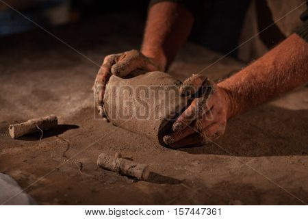 Hands of the potter knead clay. Kneads crude clay on a table