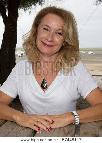 Cheerful Middle-aged Woman In Autumn At The Beach