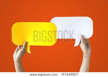 Human Hands Holding Yellow And White Speech Bubbles Over Orange Background - Balloon Speech Bubble C