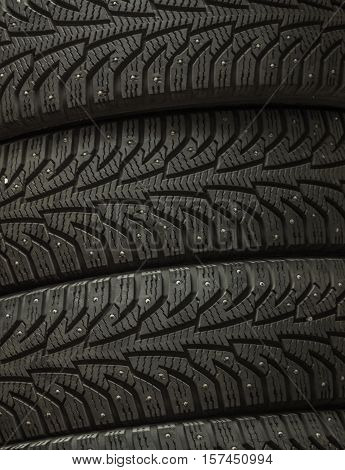 Stack of four wheel new black tires for winter car driving background macro closeup.