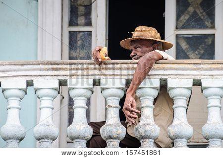 CIENFUEGOS, CUBA - MARCH 22, 2016: Elderly man with a hat eating bread in his balcony in Cienfuegos Cuba