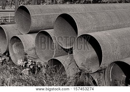 Black and white shot of rusty steel pipes found on a scrap yard.