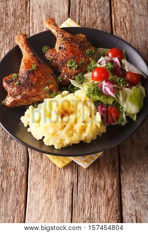 Baked Duck Leg With Mashed Potatoes Garnish And Salad Mix Close-up. Vertical