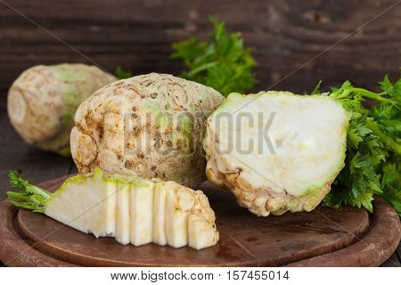 Organic celery, root celery and leaves of celery on a wooden board
