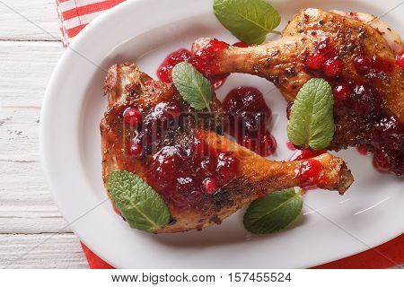 Tasty Baked Duck Leg With Cranberry Sauce And Mint Closeup On A Plate. Horizontal Top View
