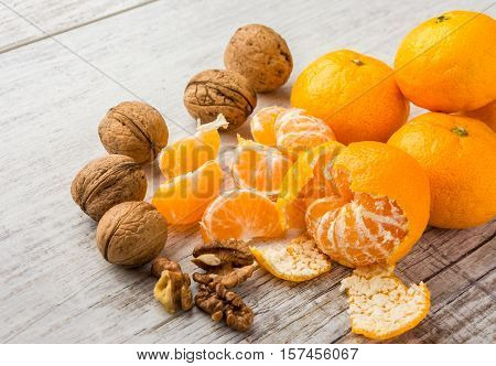 tangerines, peeled tangerine, tangerine slices and walnuts on a white wooden table