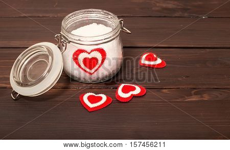 Jar with snow and a heart in him. A background from brown boards on boards several hearts are scattered the glass jar a heart from fabric lies in snow