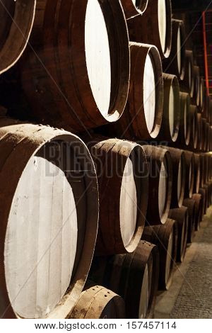 Side View Of Oak Barrels Stacked In The Old Cellar With Aging Port Wine
