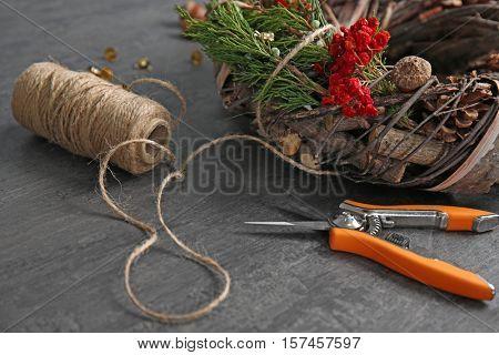 Decorative wreath and florist equipment on dark wooden background