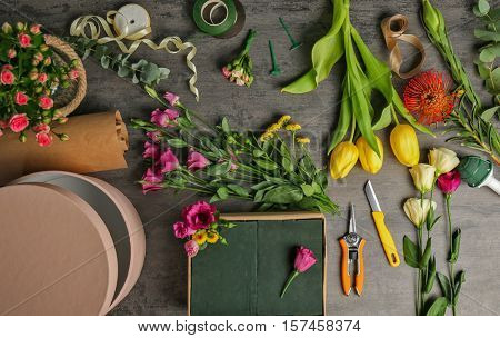 Beautiful flowers with boxes and florist equipment on dark background