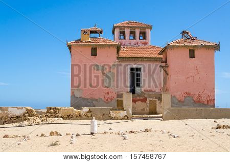 Large pink ruined mansion from Portuguese colonial times in small coastal village of Angola's Namib Desert.