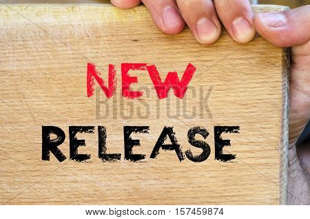 Human hand over wooden background and new release text concept