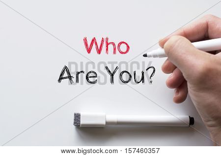 Human hand writing who are you on whiteboard