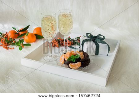 Tray with champagne in 2 crystal glasses tangerines slices chocolate and gift on background of rowan twigs tangerines all on an artificial white fur. Champagne chocolate tangerines. Horizontal.