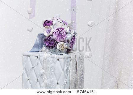 Beautiful hand made art clay bridal bouquet with purple and silver flowers lying on white side table. Copy space.