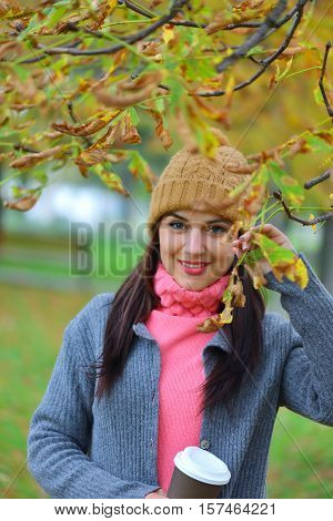 Beautiful young woman with beanie hat in park in autumn holding takeaway coffee cup smiling.